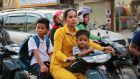A mother takes her children to school by motorbike in Phnom Penh. Photograph: Nevenka Lukin