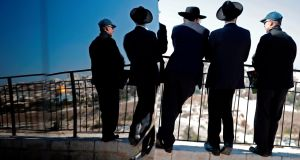 Ultra Orthodox Jews look at the city of Jerusalem from the Mount of Olives. Photograph: Thomas Coex/AFP/Getty Images