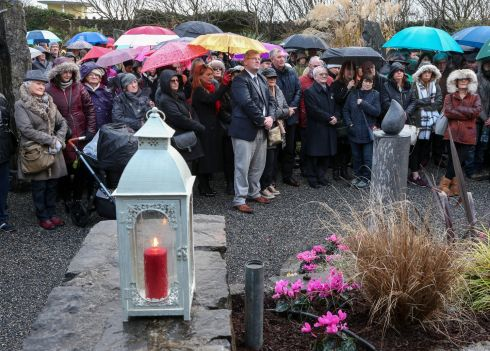 THURSDAY: A stone sculpted candle stands in front of some of the attendance at Circle of Life Garden in Salthill, Galway on Thursday. Organ donors and their families across the world were remembered, and their generosity acknowledged, in the Irish-led global commemorative initiative. Photograph: Joe O'Shaughnessy