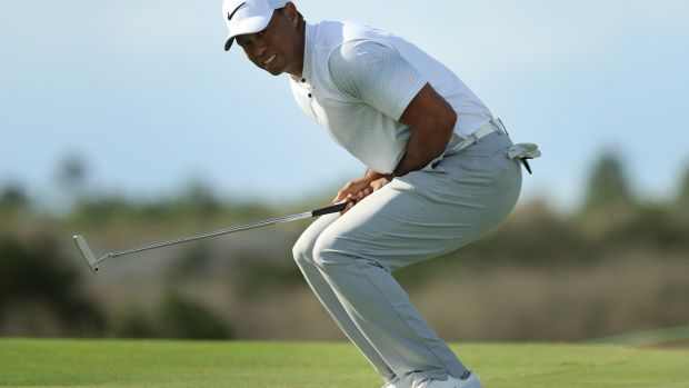 Woods reacts to a missed putt on the 12th green