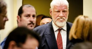 Bosnian Croat, Slobodan Praljak (right) enters the International Criminal Tribunal for the former Yugoslavia shortly before his death on Wednesday. Photograph: Robin Van Lonkhuijsen/EPA.