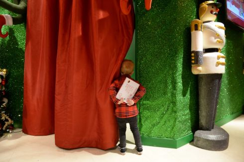 DEAR SANTA: Leo O'Keeffe (2½) from Tallaght gets a sneak peak behind Santa's curtain before delivering his letter to Santa Claus in person at Arnotts in Dublin. Photograph: Alan Betson/The Irish Times