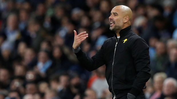 Pep Guardiola again wore a yellow ribbon in support of Catalan politicians who have been jailed for pushing for independence in Spain. Photograph: Reuters