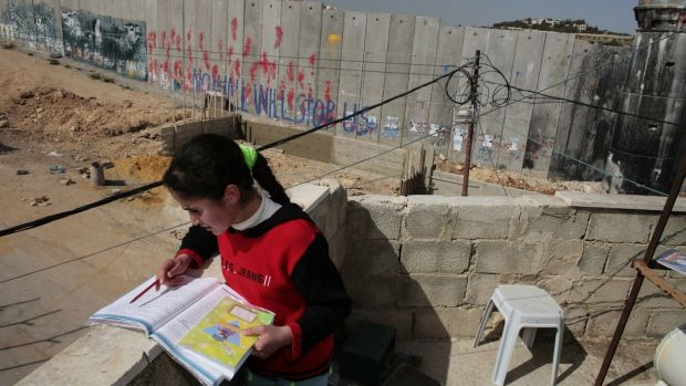 Sara, a Bethlehem native, does her homework on the balcony of the family home inside the Aida refugee camp that overlooks the concrete separation barrier in Bethlehem. Photograph: Paula Bronstein/Getty Images
