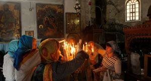 Christian pilgrims light candles inside the Church of Nativity, believed by many to be the birthplace of Jesus Christ, in Bethlehem. Photograph: AP Photo/Nasser Shiyoukhi
