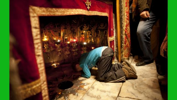 A Christian boy prays at the Grotto in the Church of the Nativity in Bethlehem, West Bank. The gold star embedded in the floor marks the spot where Jesus is believed to have been born. Photograph: Uriel Sinai/Getty Images