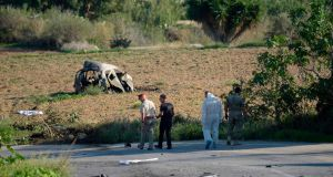 Police and forensic experts inspect the wreckage of a car bomb that killed journalist and blogger Daphne Caruana Galizia close to her home in Bidnija, Malta, on October 16, 2017.   Photograph:  AFP