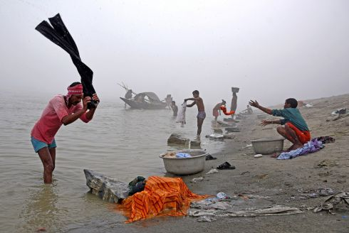 GRAND DAY FOR IT: People wash clothes on the banks of the river Brahmaputra on a foggy winter morning in Guwahati, India. Photograph: Anuwar Hazarika/Reuters