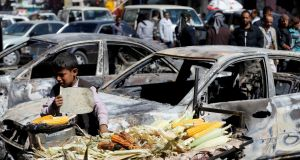 A boy sells grilled corn near cars damaged during recent clashes between Houthi fighters and forces loyal to Yemen's former president Ali Abdullah Saleh in Sana'a, Yemen, on Tuesday.  Photograph: Khaled Abdullah/Reuters