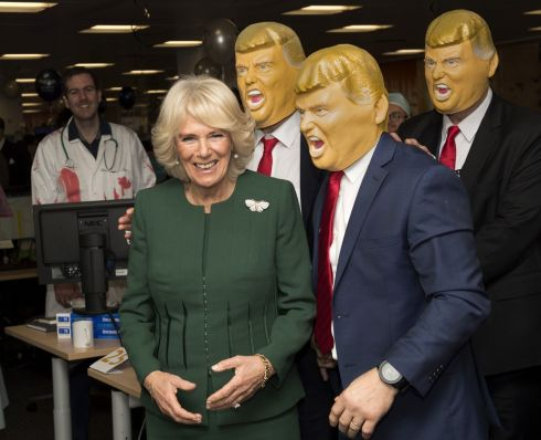 CHARITY CHUMPS: Britain's Camilla, Duchess of Cornwall, poses with staff in Donald Trump masks during her visit to the offices of city traders ICAP on their annual charity day, in London. Photograph: Arthur Edwards/AFP/Getty Images