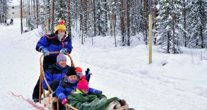 Family with children riding husky dogs sledge in Rovaniemi, Lapland, Finland
