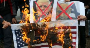 Palestinians burn posters depicting Israeli prime minister Binyamin Netanyahu and US pesident Donald Trump during a protest against the US intention to recognise the city of Jerusalem as the capital of Israel, in Rafah in the southern Gaza Strip on Wednesday. Photograph:  Ibraheem Abu Mustafa/Reuters