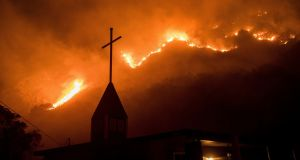 Flames from a wildfire advance down a hillside near the Springs of Life Church in Casitas Springs, California. Photograph: Noah Berger/AP