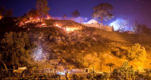 The Creek Fire burns behind a hillside near houses in the Shadow Hills neighbourhood of Los Angeles, California. Photograph: Kyle Grillot/AFP/Getty Images