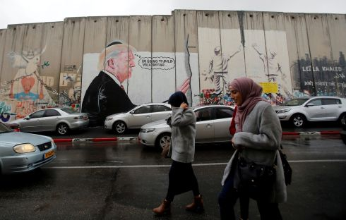 Palestinians walk past a mural depicting US president Donald Trump that is painted on a part of the Israeli barrier, in the West Bank city of Bethlehem. Photograph: Reuters