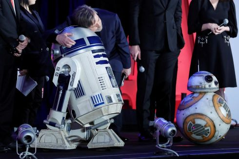 Mark Hamill hugs Star Wars character R2-D2 at a promotional event in Tokyo, Japan. Photograph: Reuters