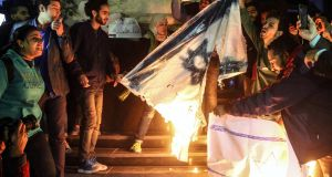 Protesters shouts slogans against US president Donald  Trump and burn Israeli flag during a protest against the Israel in Cairo. Photograph: Mohamed Elraai/ EPA