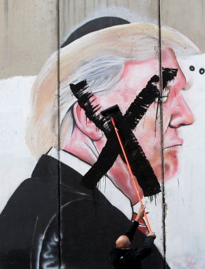 BLACK MARK: A Palestinian man crosses out a mural depicting US president Donald Trump that is painted on a part of the Israeli barrier, in the West Bank city of Bethlehem. Photograph: Mussa Qawasma/Reuters