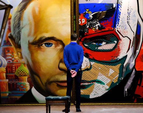 "SUPERPUTIN: A man looks at a painting depicting Russian president Vladimir Putin at the ""SuperPutin"" exhibition at UMAM museum in Moscow. Photograph: Yuri Kadobnov/AFP/Getty Images"