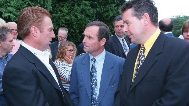 Sean Kelly, left, and Stephen Roche, right, talk with five-times Tour de France winner Bernard Hinault at a wreath-laying ceremony on the grave of Shay Elliott in Kilmacanaogue, Co Wicklow