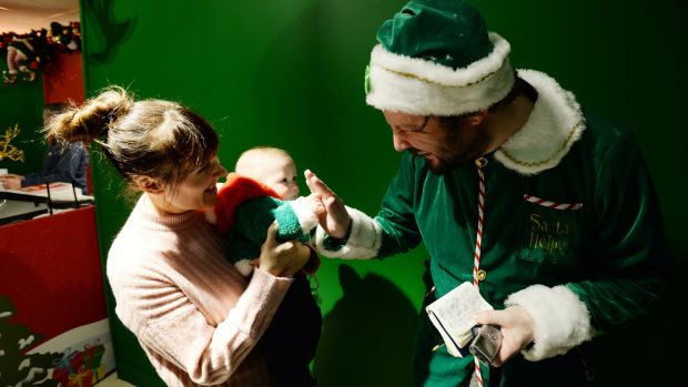 Elf Patrick Freyne with Sinead Ebbs and nine-month-old James from Tallaght at Arnotts. Photograph: Alan Betson