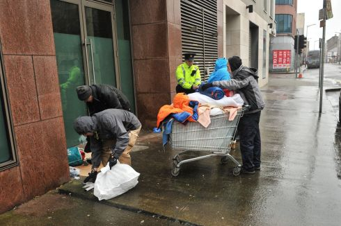 REMOVING BEDDING: Gardaí and members of Cork Simon remove bedding on Lower Oliver Plunkett street, Cork city, after a woman in her 40s had been found dead. It is believed she had been sleeping rough. Photograph: Daragh McSweeney/Provision