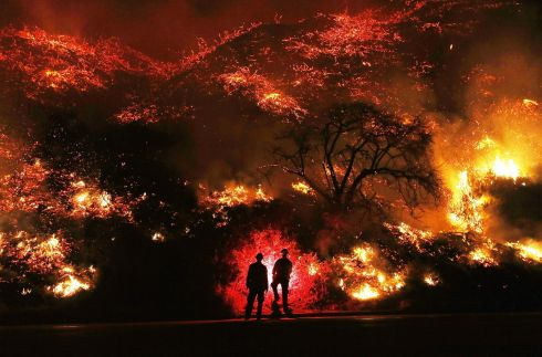 CALIFORNIA WILDFIRES: Firefighters monitor a fire along the 101 freeway north of Ventura, California. The firefighters occasionally use a flare device to burn off brush close to the roadside. Strong Santa Ana winds are rapidly pushing multiple wildfires, destroying hundreds of homes and structures. Photograph: Mario Tama/Getty Images