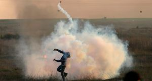 A Palestinian protester throws a tear gas canister back at Israeli forces during clashes near the Israel-Gaza border east of Gaza City. Photograph: Mahmud Hams/AFP/Getty Images