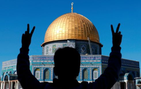 A Palestinian youth makes a V-sign for victory sign in front of the Dome of the Rock mosque at the Al-Aqsa compound in Jerusalem's Old City. Photograph: Ahmad Gharabli/AFP/Getty Images