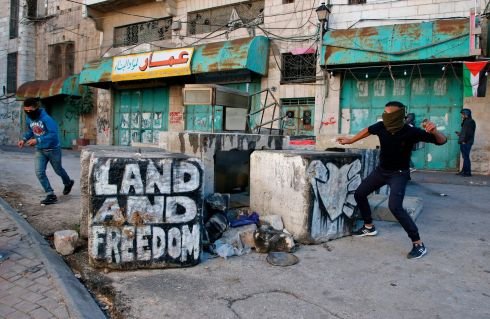 Palestinian protesters hurl rocks during clashes with Israeli forces in Hebron in the Israeli-occupied West Bank. Photograph: Hazem Bader/AFP/Getty Images