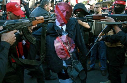 Palestinian masked gunmen belonging to the Popular Front for the Liberation of Palestine point weapons at an effigy of US President Donald Trump. Photograph: Khalil Hamra/AP Photo