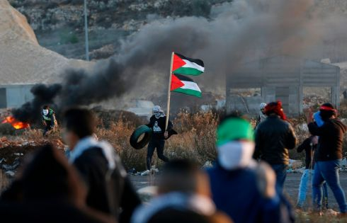 Palestinian protesters clash with Israeli forces near an Israeli checkpoint in the West Bank city of Ramallah. Photograph: Abbas Momani/AFP/Getty Images