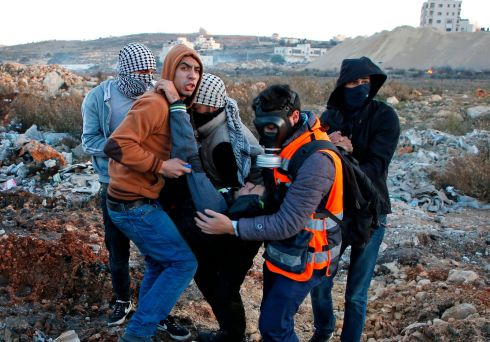 Palestinian protesters help a comradeaffected by tear gas canisters fired by Israeli forces near an Israeli checkpoint in Ramallah. Photograph: Abbas Momani/AFP/Getty Images