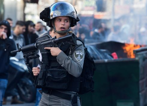 An Israeli Border policewoman near burning garbage in a dumpster during clashes on a central East Jerusalem street. Photograph: Jim Hollander/EPA