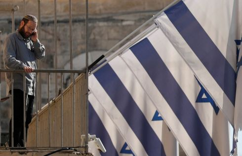 A man stands in front of Israeli flags in the Old City of Jerusalem.  Photograph: Goran Tomasevic/Reuters