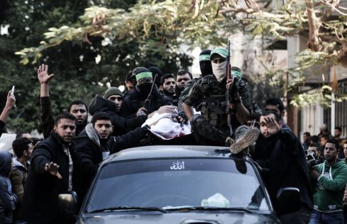 Palestinian militants of the Ezzedine al-Qassam Brigades, the armed wing of Hamas, on a car carrying the body of Mohamed al-Safadi, who was killed the previous day in an Israeli air strike, during his funeral in Gaza City. Photograph: Mahmud Hams/AFP/Getty Images