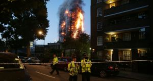 In a photo rated as one of AFP's pictures of the year 2017,  police guard  a security cordon as a huge fire engulfs the Grenfell Tower early on June 14th in west London. File photograph: Daniel Leal-Olivas/AFP/Getty Images