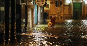 A woman makes her way  through flood waters in Cork city on  February 4th, 2014. Flooding  had hit a large part of the country for a second day. File photograph: Niall Carson/PA Wire