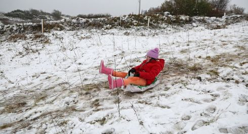 GO DOWNHILL: Robyn Keane slides down a hill on a bag of straw following snow in the Rahoon area in Galway. Photograph: Joe O'Shaughnessy