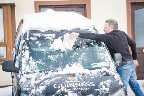 SNOWED UNDER: Paddy Robinson clears snow off his van in Grattan Park, Claremorris, Co Mayo. Photograph: Keith Heneghan