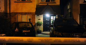 A garda stands outside a house in Woodville Avenue in Lucan, Co Dublin, on Sunday night, where the remains of a man were found. Photograph: Aidan Crawley
