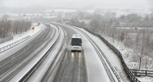A coach drives through the snow on the M7 motorway  near Birdhill, Co Limerick on Sunday.  Photograph: Niall Carson/PA Wire