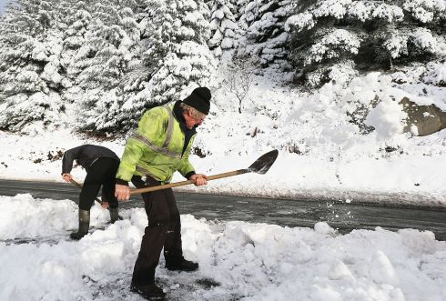 YOU MISSED A SPOT: James Williams and Sean Cullen clearing a driveway following heavy snow on the Glencullen Road. Photograph: Stephen Collins/Collins Photos