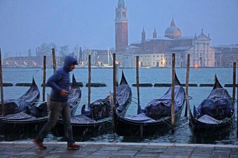 ON ICE: A man walks past gondolas covered in snow, during wintry weather in Venice, Italy. Photograph: Andrea Merola/EPA