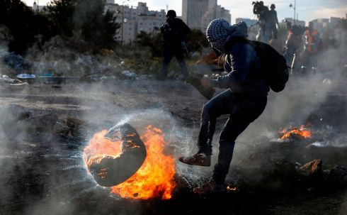 STOKING THE FIRE: A Palestinian protester kicks a flaming tire during clashes with Israeli forces in the West Bank city of Ramallah amid unrest over US president Donald Trump's declaration of Jerusalem as Israel's capital. Photograph: Abbas Momani/AFP/Getty Images