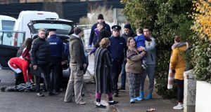Local residents and Garda officers at Parslickstown Gardens in Mulhuddart, west Dublin, near the scene of a shooting on Monday. Photograph:  Niall Carson/PA Wire