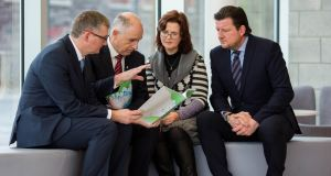 At the University of Limerick, Prof Shane Kilcommins,  Minister of State  David Stanton,  Dr Catherine Naughton and Prof Sean Redmond, examine a report on children and crime. Photograph: Alan Place