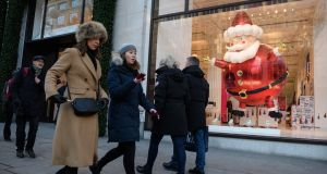 Christmas shoppers walk past festive window displays on Oxford Street in London on Tuesday. Inflation rose to 3.1% in November. Photograph: Leon Neal/Getty Images