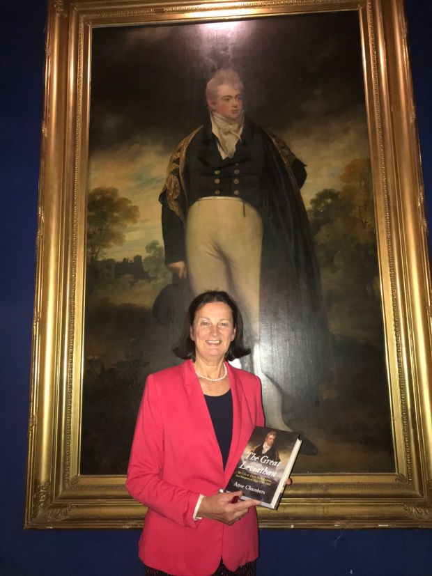 Anne Chambers with her biography of Lord Sligo in front of his portrait in Westport House