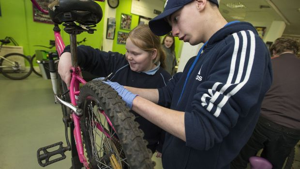 Patrick and his sister Katelyn repairing her bike at Bradog Youth Service. Photograph: Dave Meehan